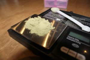 A digital scale with a pile of kratom on it