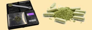 A digital scale with a pile of green powder and a measuring spoon on one side and a pile of green powder and capsules on the other with a yellow background.
